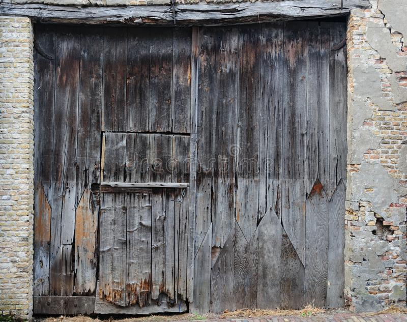 Old, dirty and weathered closed wooden barn door stock photography