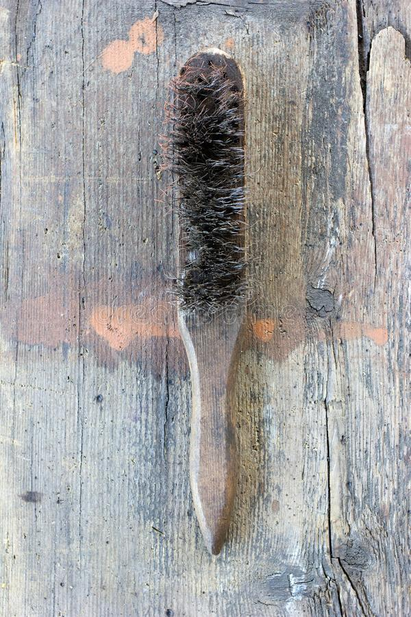 Old, dirty wire brush against wooden plank. stock photo