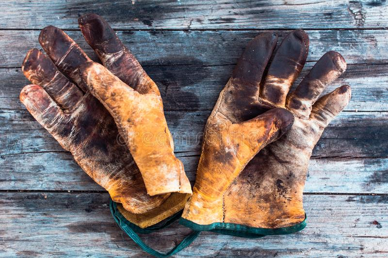 Old and dirty working gloves over wooden table,  gloves for each finger royalty free stock photos