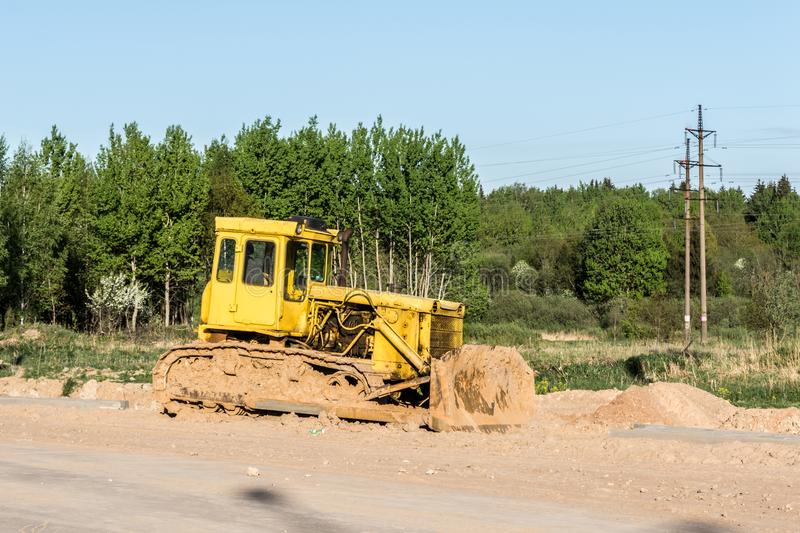 The old dirty yellow bulldozer, road construction in the forest stock photography