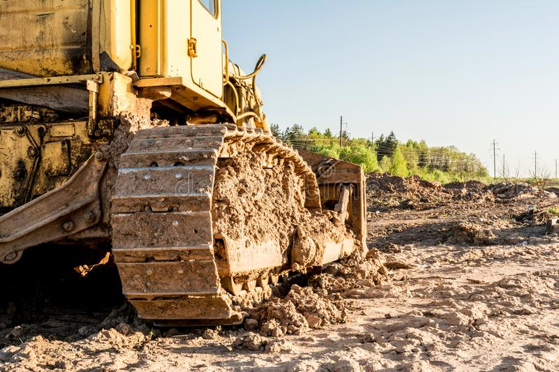 Old dirty yellow crawler bulldozer, rear view, the construction machine is lit by the rays of the setting sun. Abstract background stock image