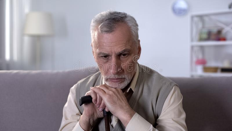 Old disabled man with walking stick sitting on couch, diseases at retirement age stock photography