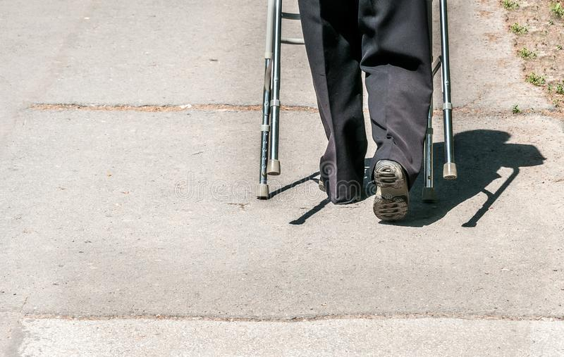 Old disabled woman walking alone and depressed on the street in the city helped by adjustable walker stick or cane royalty free stock photos