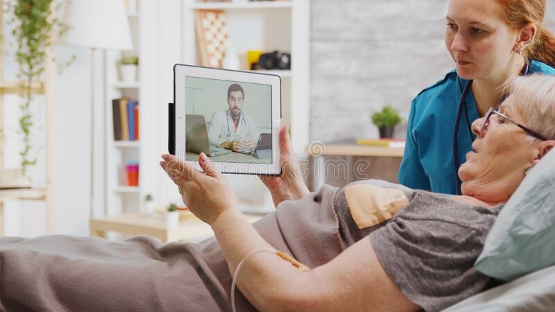 Old disabled woman lying in hospital bed having an online video call with a doctor royalty free stock images