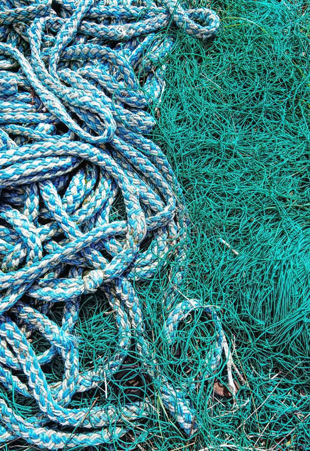 Old discarded fishing net and rope. Contrasting blue and green colours of fishing net and rope, left on a beach royalty free stock photography