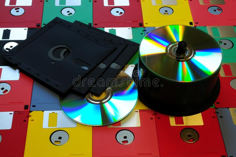 Old diskette 5 25 inches with 3.5 floppy disks of various colors with modern DVD. royalty free stock image