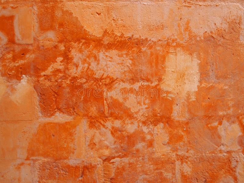 Old distressed patched orange stone wall painted in different shades of faded stained bright ochre paint royalty free stock photography