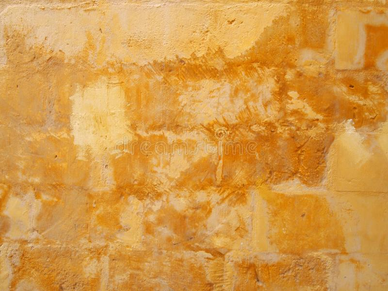 Old distressed patched yellow stone wall painted in different shades of faded stained bright yellow paint. An old distressed patched yellow stone wall painted in royalty free stock photos