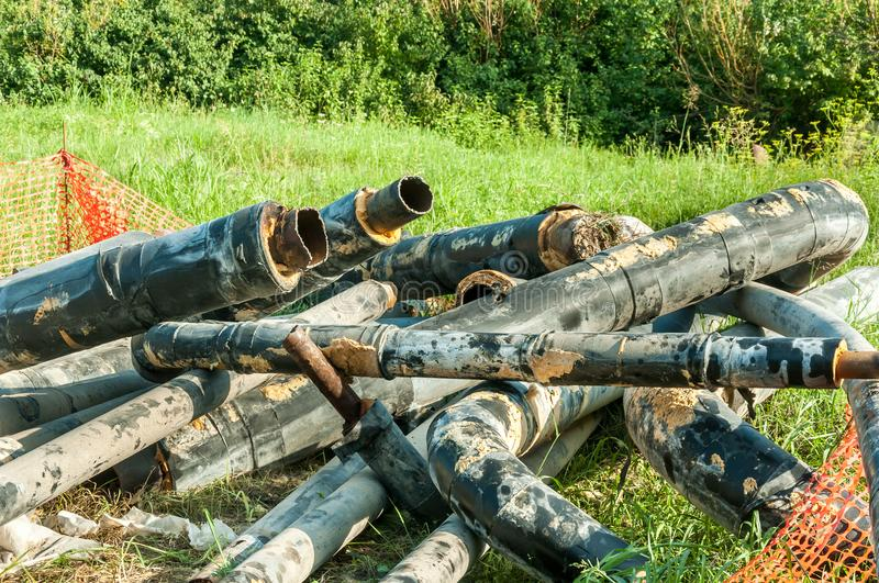 Old district heating pipes with insulation removed from the ground to be replaced with new pipeline system selective focus.  stock photo
