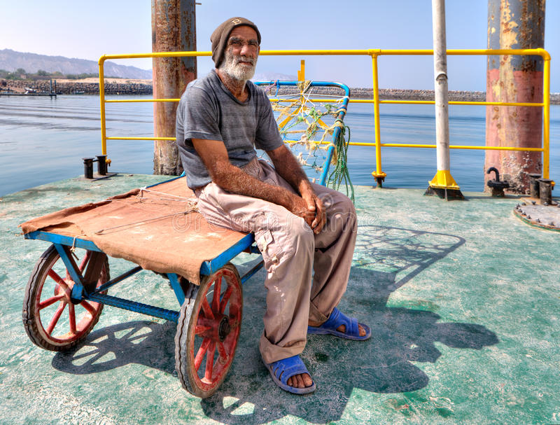 Old docker sits on handcart in the port, South Iran. royalty free stock photography