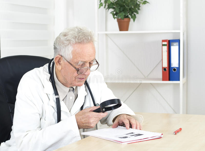 Old doctor with loupe study a literature. Old doctor with glasses study a literature in consulting room stock photography