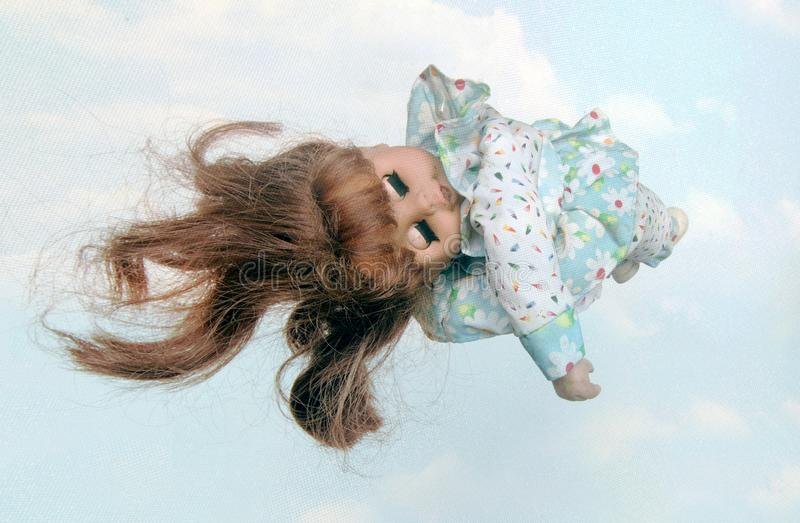 Old doll sleeping in the clouds. Close up stock photo