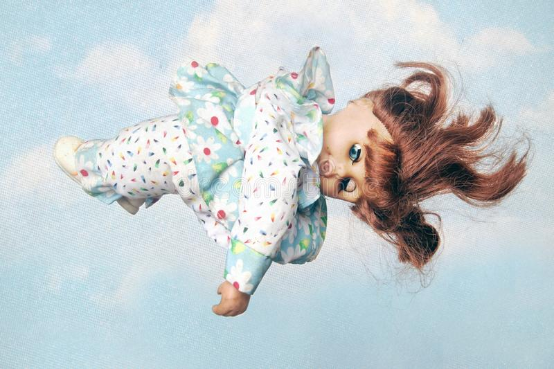 Old doll sleeping in the clouds. Close up royalty free stock image