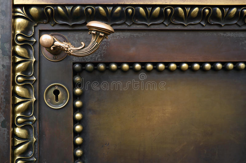 Old door and curved handle. Old brass door with a nice curved handle royalty free stock image