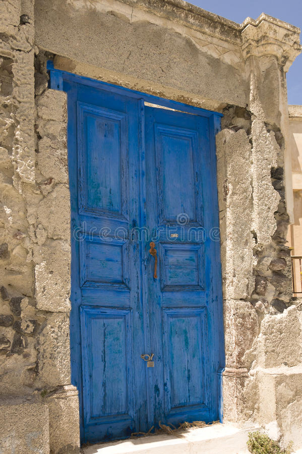 Old door in Greece. Wooden grungy blue door painted and locked in Chania, Greece royalty free stock image