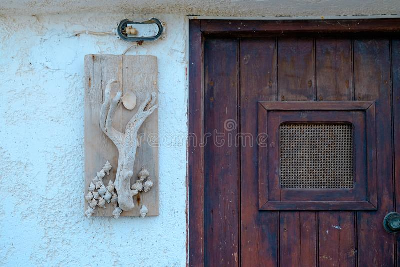 Old door in greece. Old brown wooden door against a white wall in Greece stock image