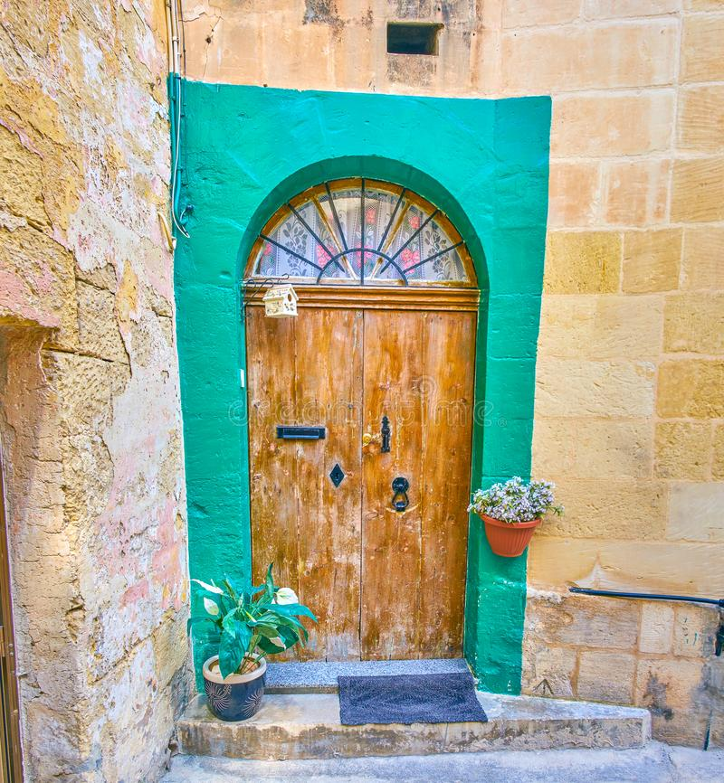The shabby door in old town of Mosta, Malta. The old door with half round window above and flowers in pots could be found in old town of Mosta, Malta stock photos