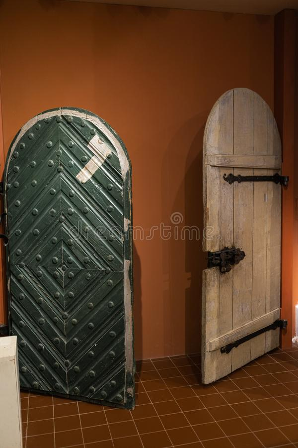Old door holes and handles - Wooden entrance on brick walls - Handles made of metal stock photos