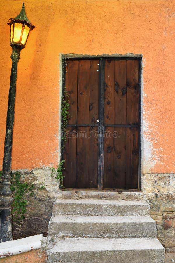 Old door illuminated with orange light lamp royalty free stock photography
