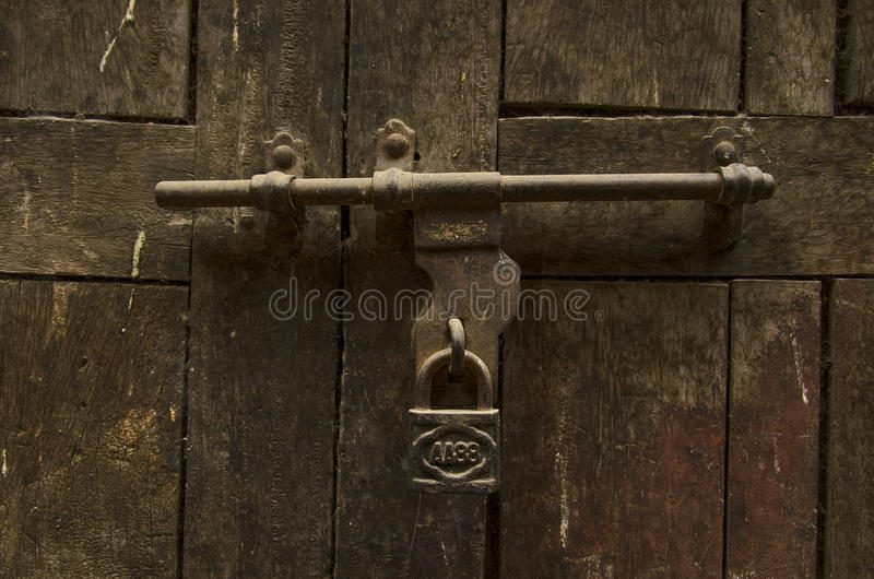 Old door. Kathmandu. Nepal. Old door. Latch and padlock. Old brown wood wooden boards with remnants of red paint. Kathmandu. Nepal stock photo