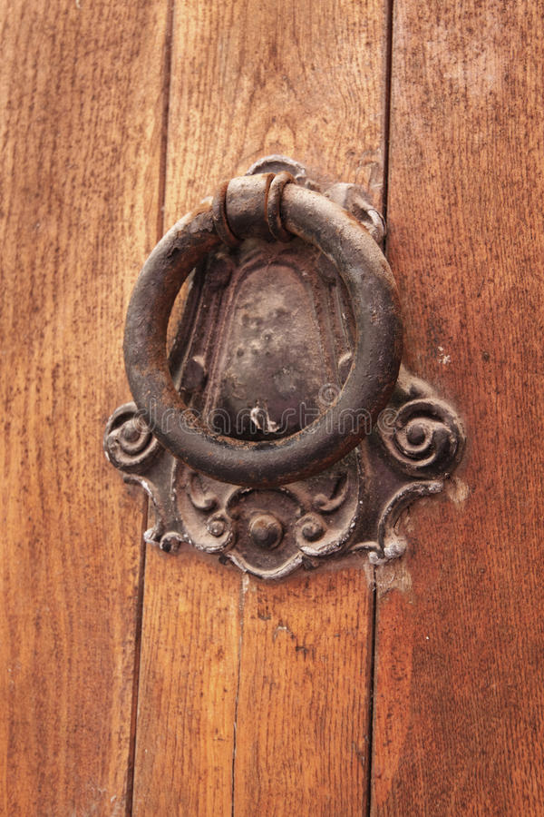 Old door knocker and as a bell to call people. Old wooden door knocker and as a bell to call people royalty free stock image