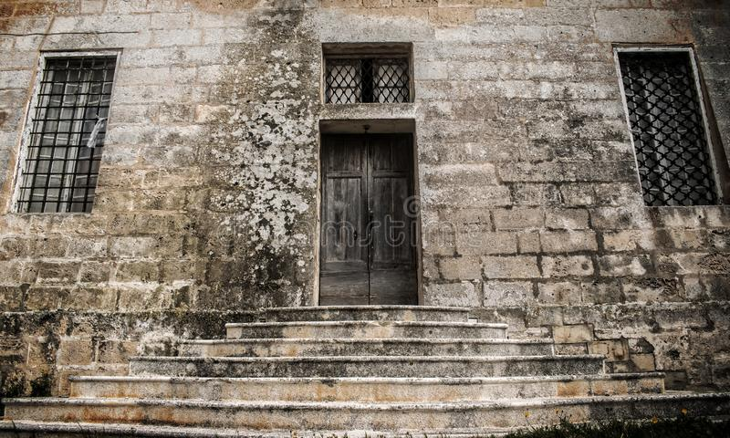 Old Door in Limestone Wall. An old wooden door and two iron windows within a typical Maltese limestone wall royalty free stock image