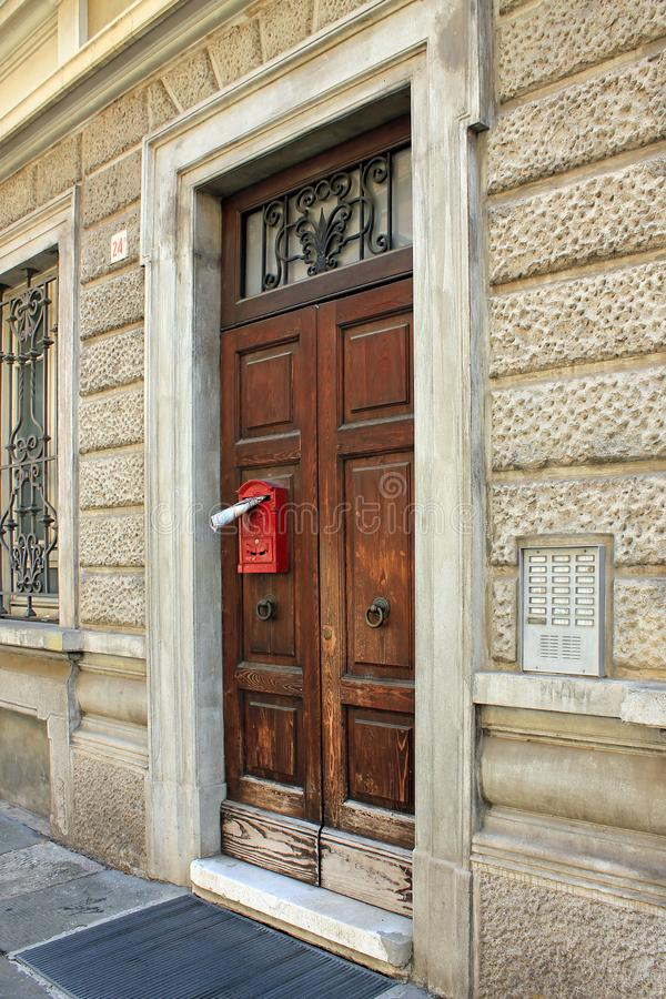 An old door with a mailbox and a newspaper. Old brightly painted door with mailbox, newspaper and beautiful door handle in Italy royalty free stock images