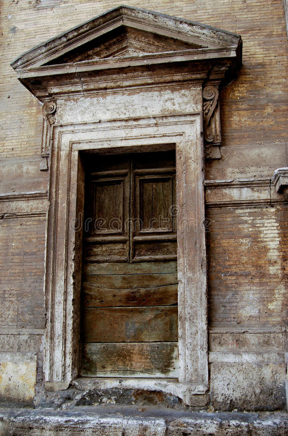 Old Door in Rome Italy. Harsh weather and the years have taken their toll on this quaint wooden door in Rome, Italy royalty free stock photo