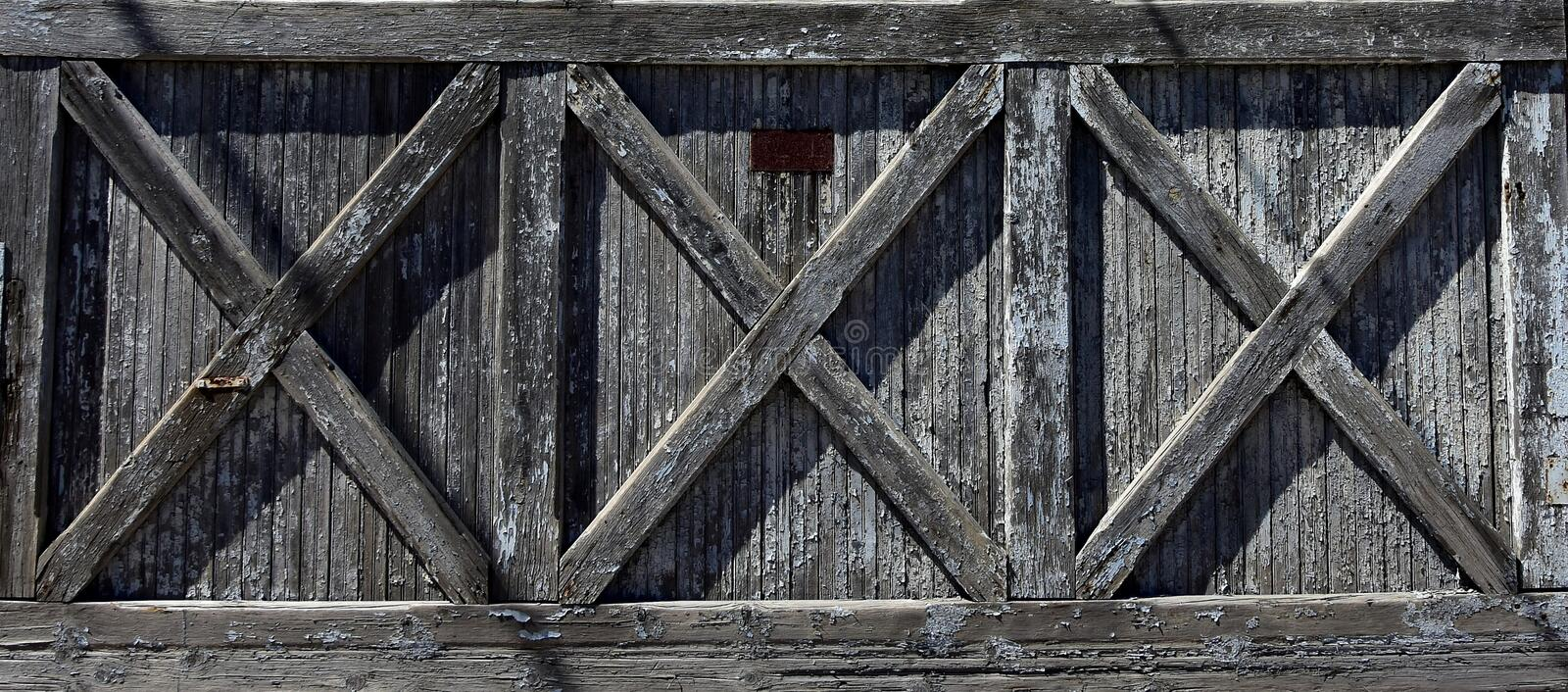 Old door with three X shaped supports. A rustic framed barn door with the wood weathered to a variety of gray shaded color ranges in a triple X pattern stock photography