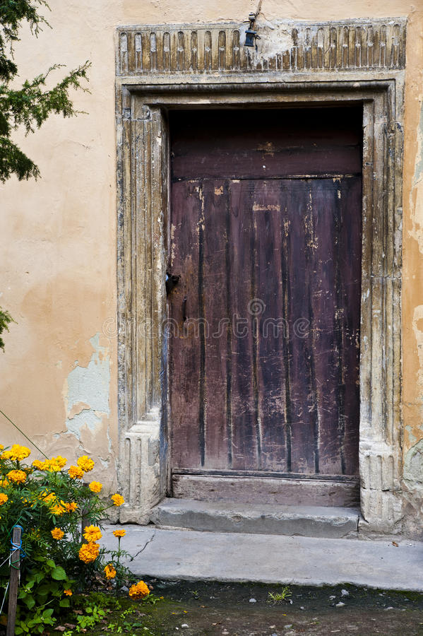 Old door in a wall. Old brown scraped door in a wall of an old building, and yellow flowers in a corner of image stock photos
