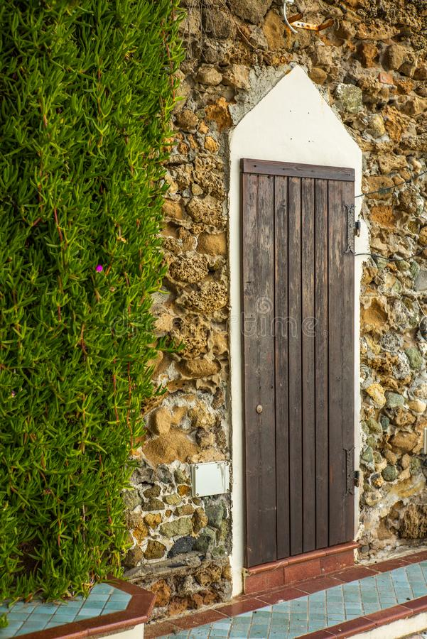 An old door on a wall with sea rocks on the sea walk in Castiglioncello in Tuscany stock images