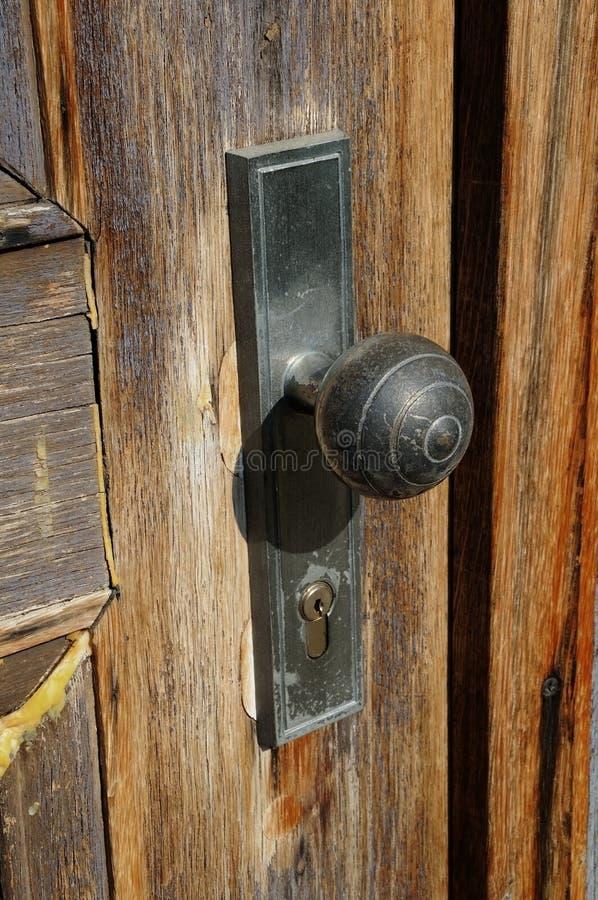 Old doorknob. An old doorknob at an old wooden front door stock image