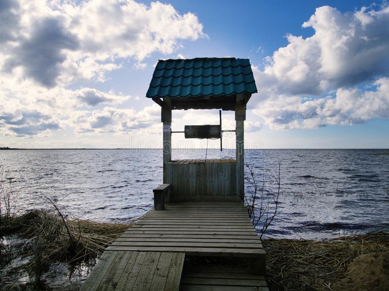 Old draw well on shore of lake stock image