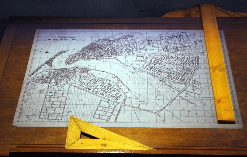 Old drawing of the city of Dubai in the 60s placed on an architect's table with wooden geometry tools. stock photos