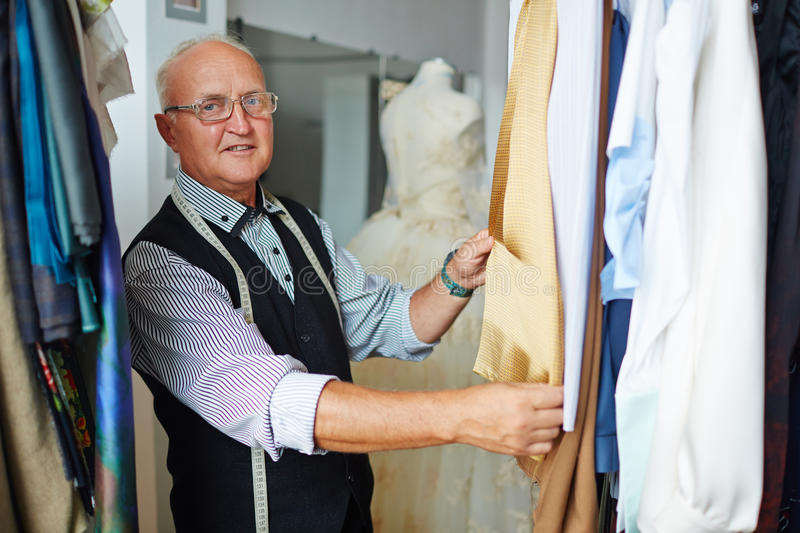 Old Dress-Maker Showing garments in Studio. Portrait of old grey-haired tailor presenting custom made garments on hangers in small atelier shop stock photo