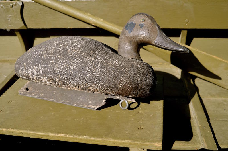 Old duck decoy in a duck rowboat. An old canvas layered duck mallard decoy casts its shadow against the oar in a duck boat stock image
