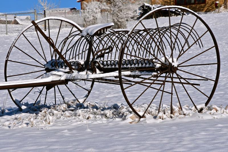 An old dump rake in the snow. An old steel rake left in the snow on a ranch pasture royalty free stock images