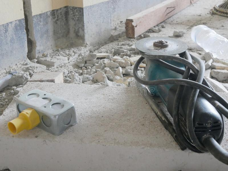 Old dusty angle grinder, with a diamond cutting disc, and an electrical back box placed on a lightweight concrete block royalty free stock photography