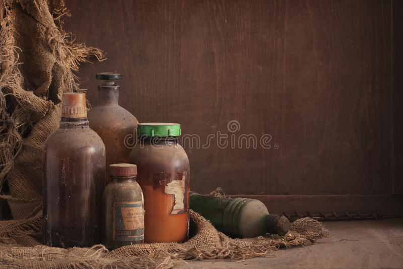 Old dusty bottles still life. A still life composition with old dusty bottles on wood background, empty space for text stock photography