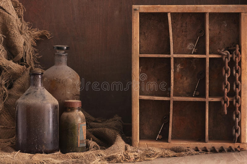 Old dusty bottles still life. A still life composition with old dusty bottles on wood background, empty space for text royalty free stock photo
