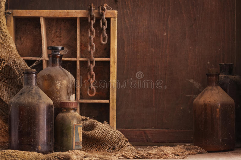 Old dusty bottles still life. A still life composition with old dusty bottles and other objects on wood background, empty space for text stock image