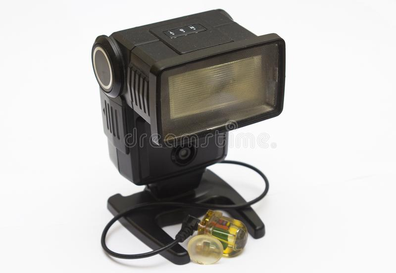 An old dusty National photographic flash unit from the film era that has been adapted for permanent use as a remote flash unit wit. H a peanut slave flash royalty free stock photography