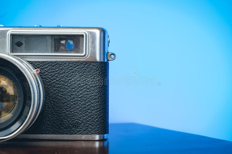 Old and dusty vintage camera on wooden desk over blue background stock images