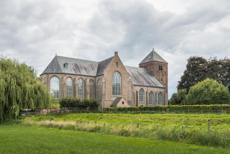 Old Dutch church on a cloudy day. Ancient Protestant Church in a small village in the Netherlands with a tower from the 13th century, and incidentally, built royalty free stock photography
