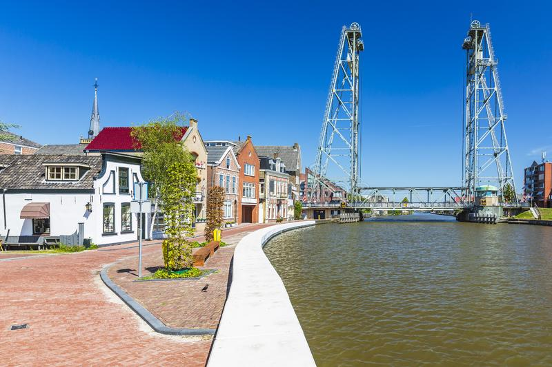 Old Dutch historic houses and vertical lift bridge crossing the river Gouwe at Boskoop, the Netherlands. View over water at a vertical lift bridge crossing the royalty free stock images