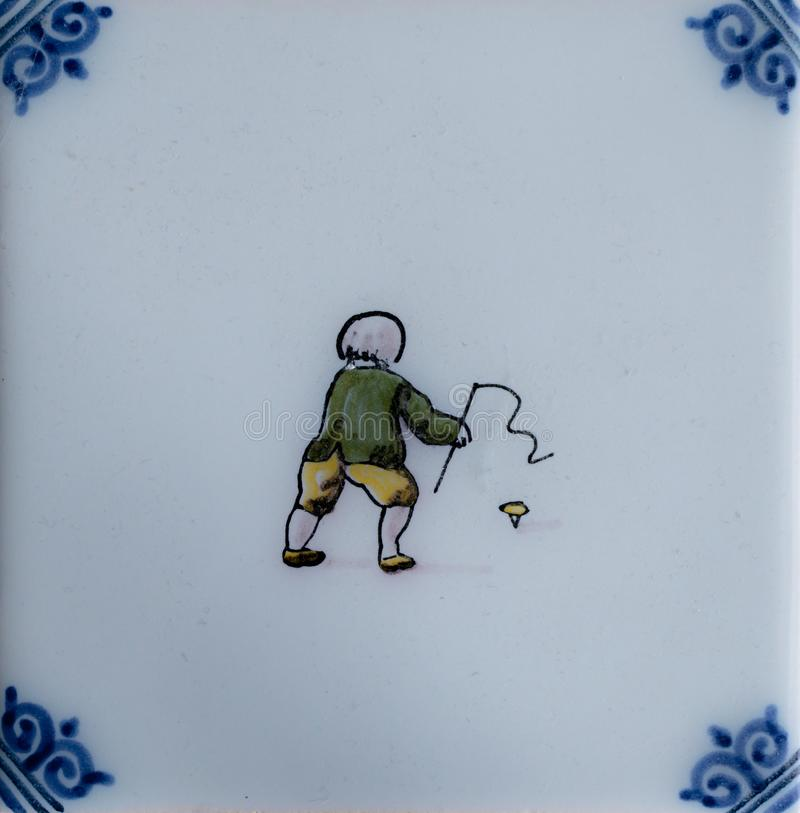 Old dutch tile showing a kid witha peg-top stock images