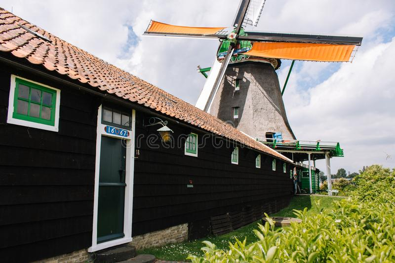 Old dutch windmill and wooden house in historical village. Holland mill in field with ancient building. Zaanse Schans, Netherlands - 06/14/2019: Old dutch royalty free stock image