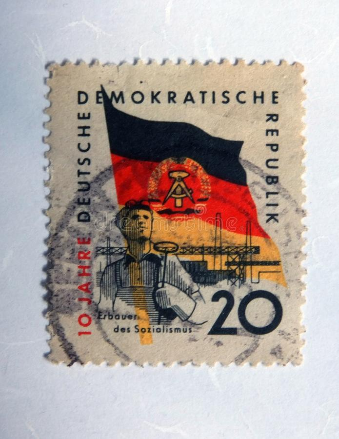 An old east german postage stamp with an image of a steel worker against the flag of the gdr stock photo