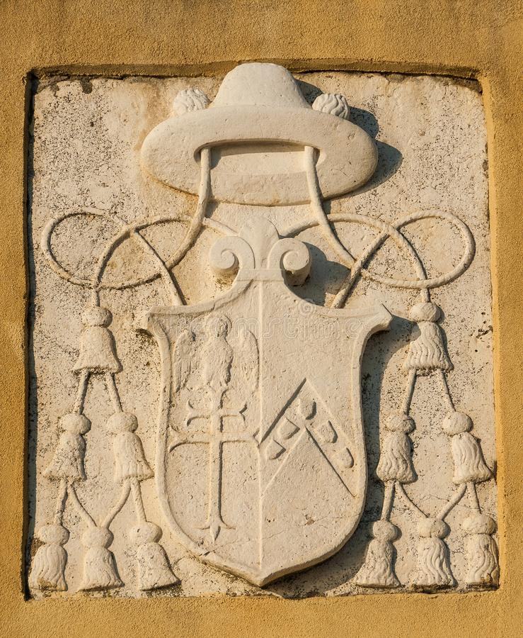Ecclesiastical symbol in Venice. Old ecclesiastical emblem of cardinal or bishop with tassels on a wall in Venice stock photos