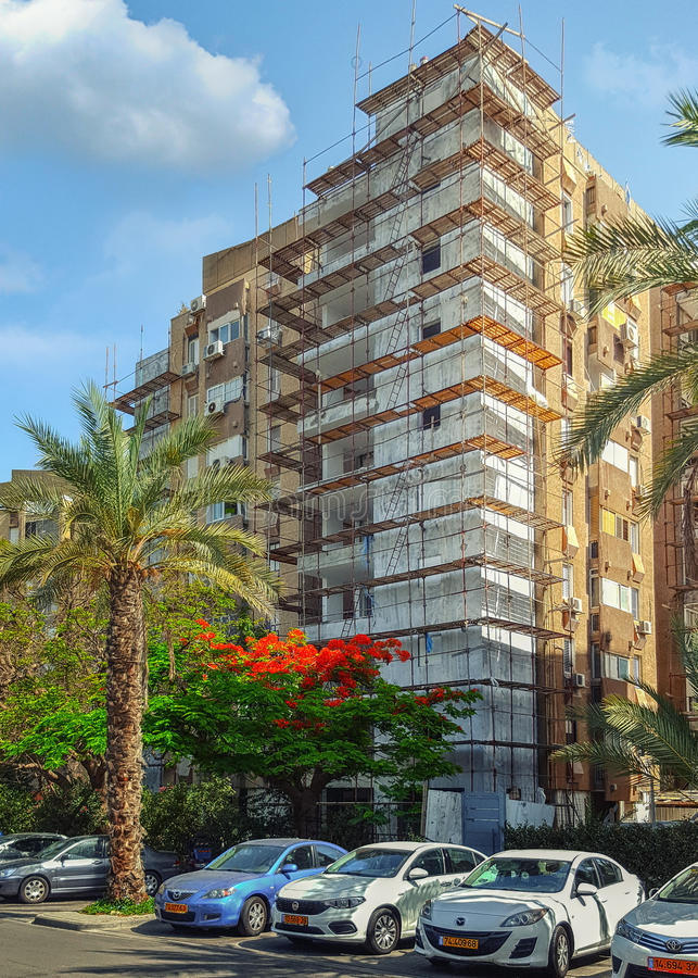 Old eight-story condominium under reconstruction. Holon, Israel - May 26, 2016: Old eight-story residential condominium building is being framed by steel and stock photos